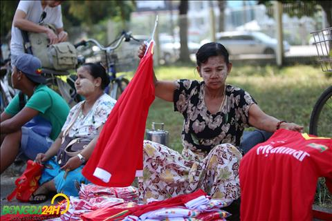 Mot phu nu ban ao dau cua DT Myanmar ben ngoai khu vuc xep hang mua ve.