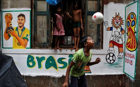 Mot cau be choi dua voi trai bong, ben canh tranh tuong co hinh anh Neymar tai Kolkata, An Do.